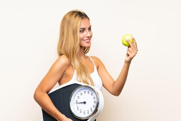 Jovem mulher loira com máquina de pesagem e com uma maçã