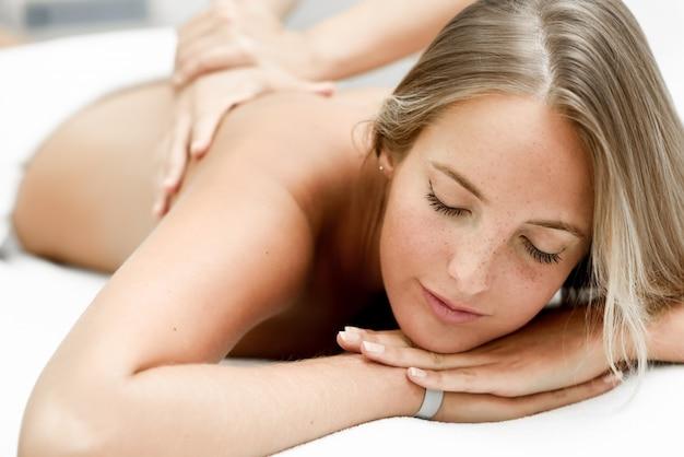 Jovem, mulher loira, com massagem no salão de spa