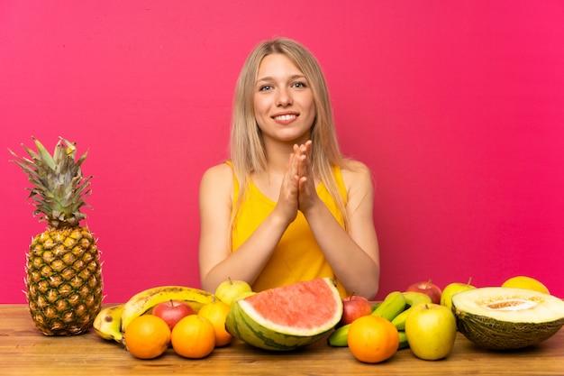 Jovem mulher loira com muitas frutas aplaudindo