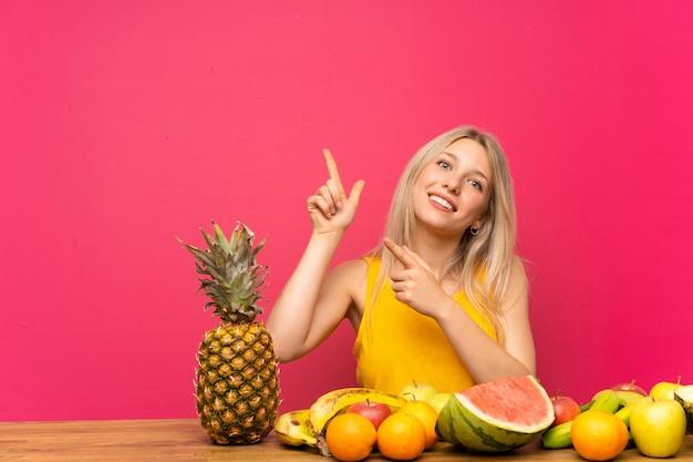 Jovem mulher loira com muitas frutas apontando com o dedo indicador uma ótima idéia