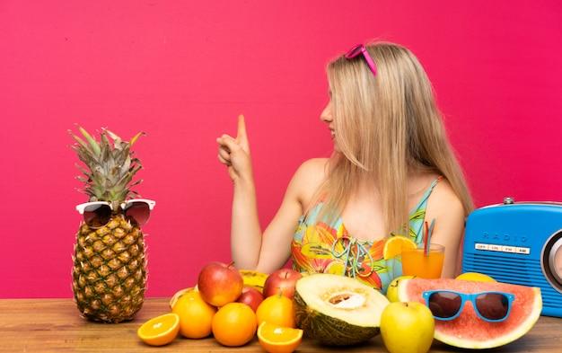 Jovem mulher loira com muitas frutas, apontando para trás com o dedo indicador