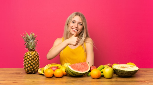 Jovem mulher loira com muitas frutas, dando um polegar para cima gesto