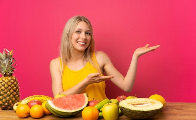 Jovem mulher loira com muitas frutas, estendendo as mãos para o lado para convidar para vir