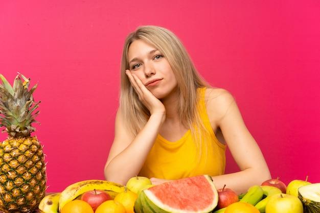 Jovem mulher loira com muitas frutas infelizes e frustradas