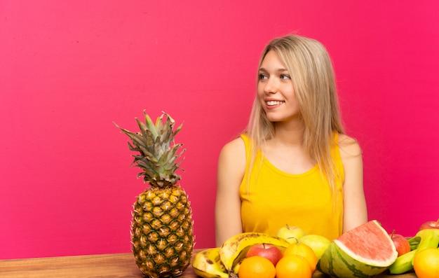 Jovem mulher loira com muitas frutas, olhando para o lado