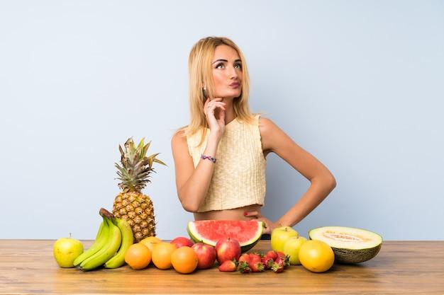 Jovem mulher loira com muitas frutas pensando uma idéia