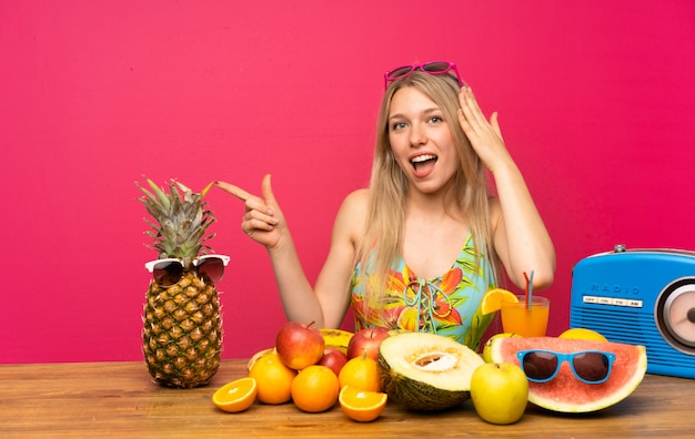 Jovem mulher loira com muitas frutas surpreso e apontando o dedo para o lado