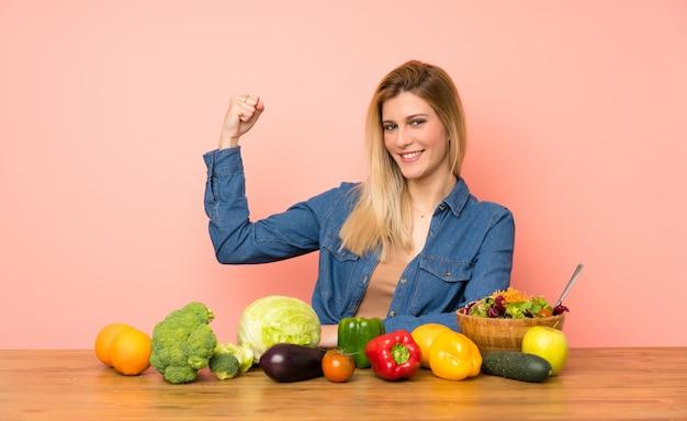 Jovem mulher loira com muitos legumes, fazendo um gesto forte
