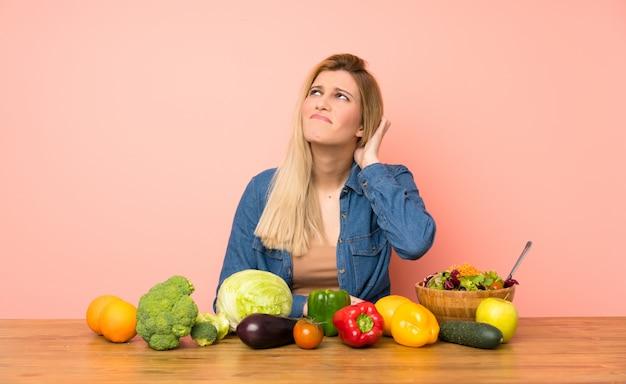 Jovem mulher loira com muitos legumes, tendo dúvidas