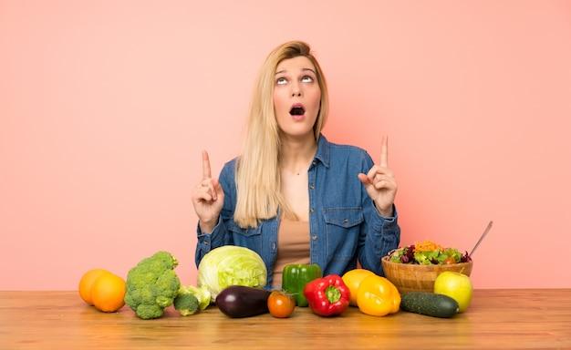 Jovem mulher loira com muitos vegetais surpresos e apontando para cima
