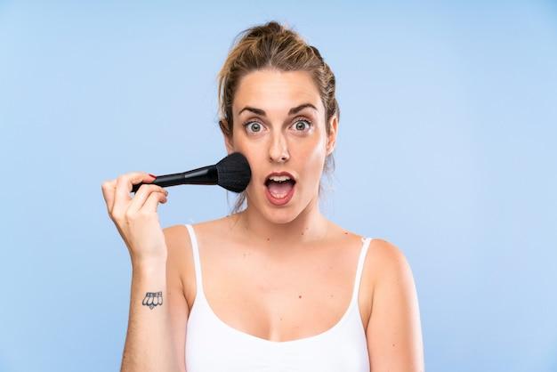 Jovem mulher loira com pincel de maquiagem, fazendo o gesto de surpresa