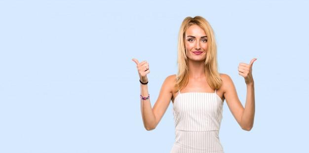 Jovem mulher loira com polegares para cima gesto e sorrindo sobre azul isolado