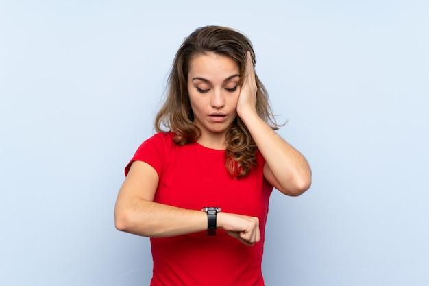 Jovem mulher loira com relógio de pulso e surpreso