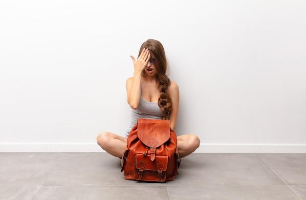 Jovem mulher loira com sono, entediada e bocejando, com dor de cabeça e uma mão cobrindo metade do rosto sentado no chão