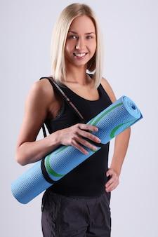 Jovem mulher loira com tapete de ioga.