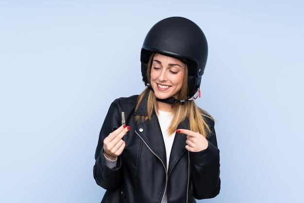 Jovem mulher loira com um capacete de moto e uma chave sobre parede azul isolada
