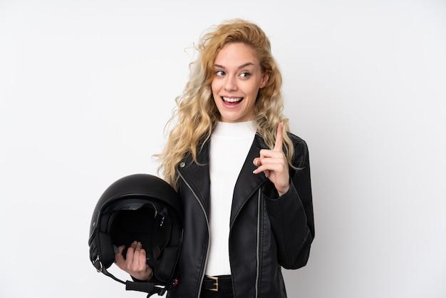 Jovem mulher loira com um capacete de moto em branco com a intenção de perceber a solução enquanto levanta um dedo