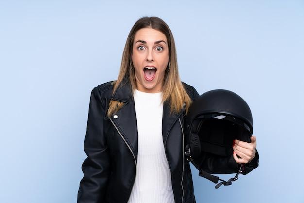 Jovem mulher loira com um capacete de moto sobre parede azul isolada com surpresa e expressão facial chocada