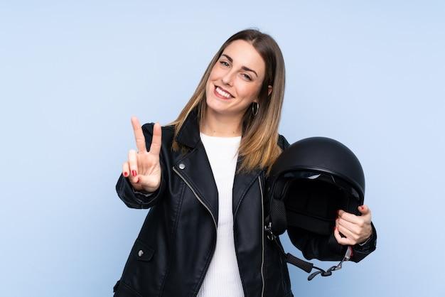 Jovem mulher loira com um capacete de moto sobre parede azul isolada, sorrindo e mostrando sinal de vitória