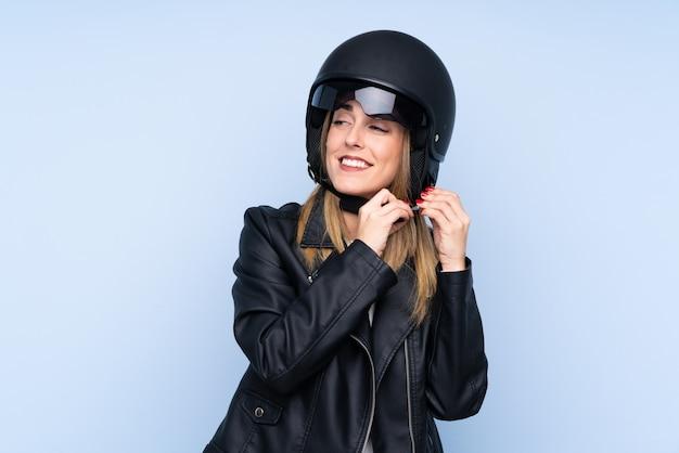 Jovem mulher loira com um capacete de moto sobre parede azul isolada