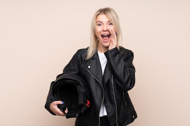 Jovem mulher loira com um capacete de moto sobre parede isolada, gritando com a boca aberta