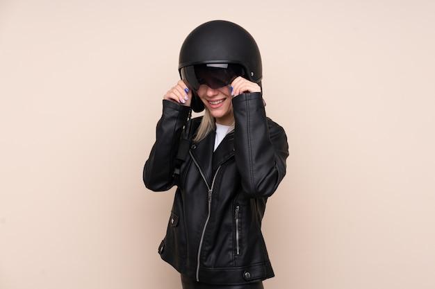 Jovem mulher loira com um capacete de moto sobre parede isolada