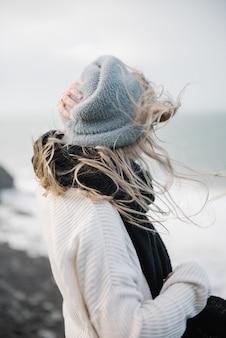 Jovem mulher loira com um chapéu, caminhando em uma costa rochosa em um clima ventoso