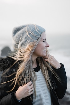 Jovem mulher loira com um chapéu se divertindo na praia em um tempo ventoso