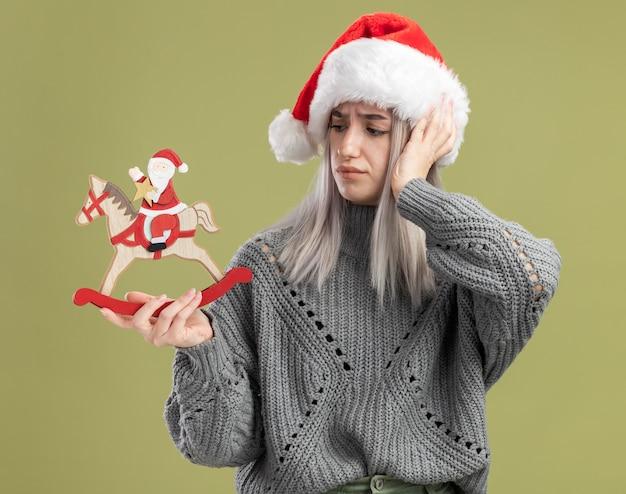 Jovem mulher loira com um suéter de inverno e um chapéu de papai noel segurando um brinquedo de natal, olhando para ele confuso com a mão na cabeça em pé sobre a parede verde