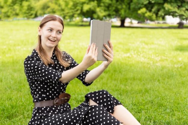 Jovem mulher loira com um vestido de verão faz selfie em um tablet enquanto está sentado na grama verde em um parque