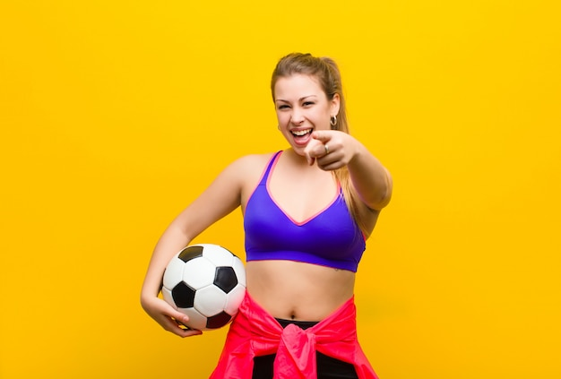 Jovem mulher loira com uma bola de futebol. conceito de esporte