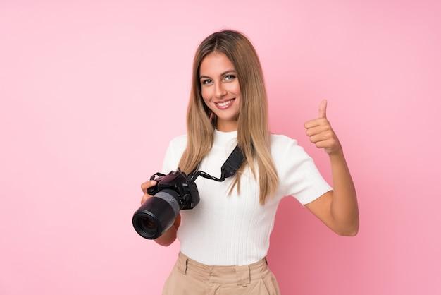 Jovem mulher loira com uma câmera profissional e com o polegar para cima