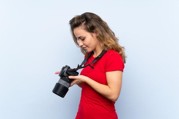 Jovem mulher loira com uma câmera profissional