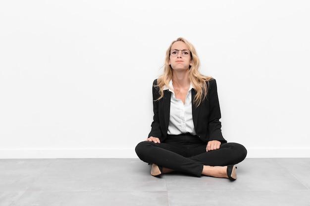 Jovem mulher loira com uma expressão pateta ,, surpresa, bochechas inchadas, sentindo-se empalhado, gordo e cheio de comida, sentada no chão