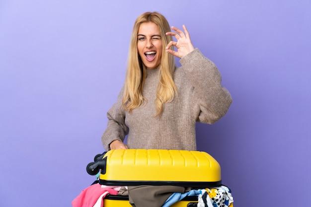 Jovem mulher loira com uma mala cheia de roupas sobre parede roxa isolada mostrando sinal okey com os dedos