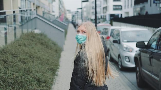 Jovem mulher loira com uma máscara médica escapando de alguém na rua.
