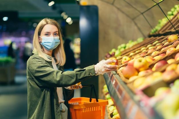 Jovem mulher loira com uma máscara médica protetora escolhe escolhe legumes frutas maçã no balcão do supermercado. compras femininas no mercado perto de uma loja de departamentos com uma cesta nas mãos
