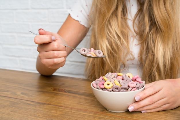 Jovem mulher loira com uma tigela de cereais
