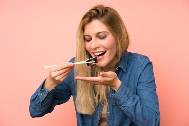 Jovem mulher loira comendo sushi parede rosa