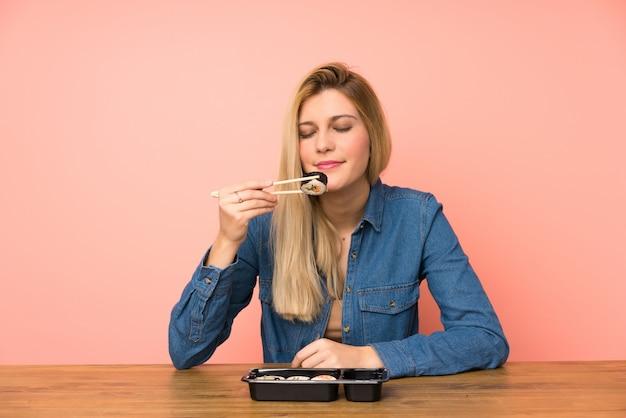 Jovem mulher loira comendo sushi