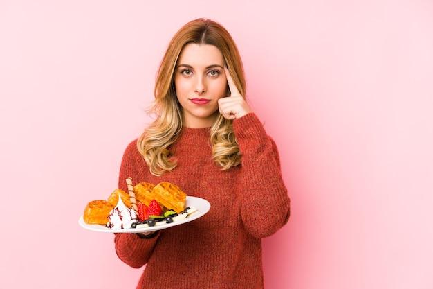 Jovem mulher loira comendo uma sobremesa waffle isolada apontando o templo com o dedo, pensando, focada em uma tarefa.