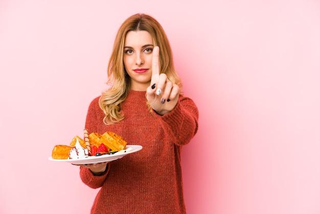 Jovem mulher loira comendo uma sobremesa waffle isolada mostrando o número um com o dedo.