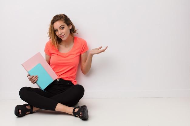 Jovem mulher loira contra a parede com livros