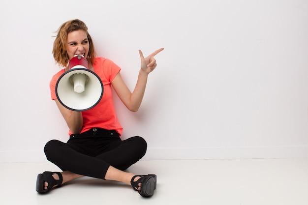 Jovem mulher loira contra parede de cor lisa com um megafone