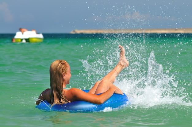 Jovem mulher loira de biquíni azul para trás na água do mar parada com círculo de natação e olhando para o navio no horizonte num dia ensolarado de verão. conceito de felicidade, férias e liberdade