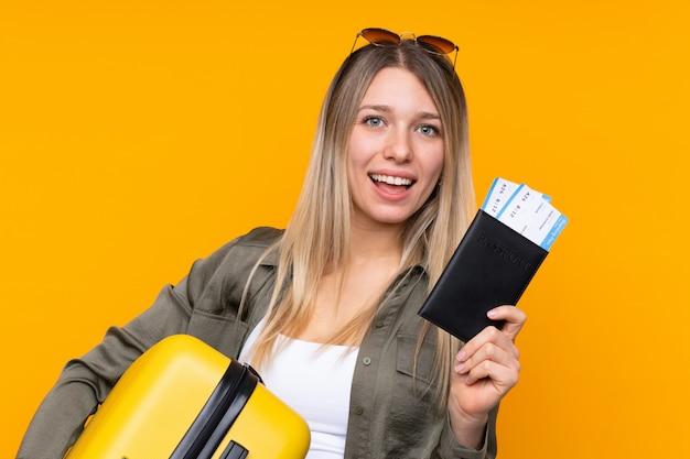 Jovem mulher loira de férias com mala e passaporte
