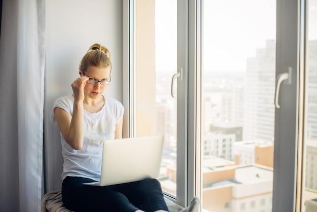 Jovem mulher loira de óculos em t-shirt branca, trabalhando no laptop em casa, sentada no parapeito da janela. freelancer e empresa remota. plano de fundo da janela. copie o espaço.