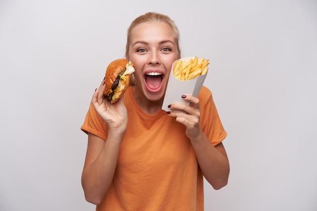 Jovem mulher loira de olhos azuis muito feliz com penteado casual olhando animadamente para a câmera com os olhos arregalados e a boca aberta, segurando hambúrguer e batatas fritas em pé sobre um fundo branco