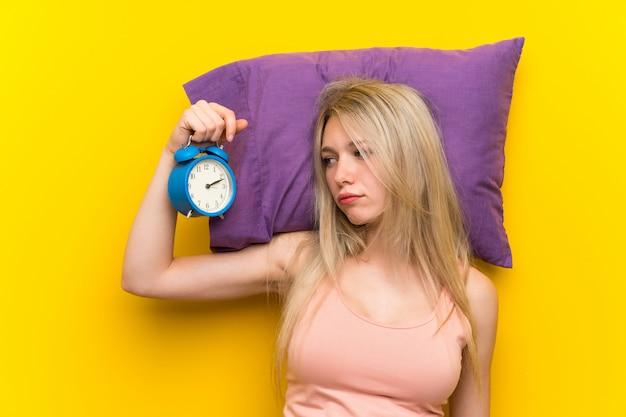 Jovem mulher loira de pijama segurando o relógio vintage