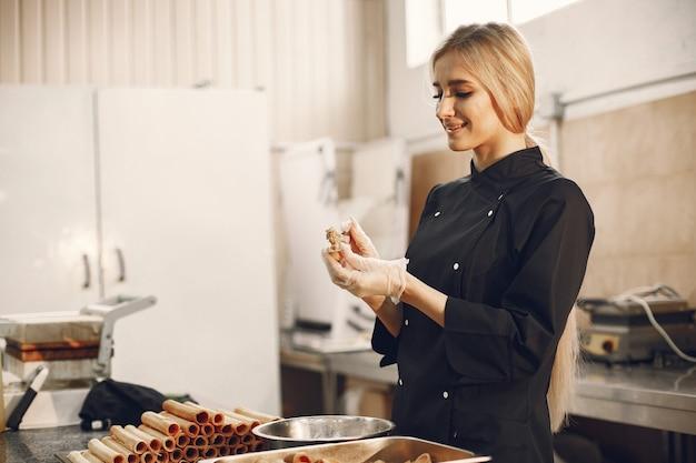 Jovem mulher loira de uniforme preto na cozinha do restaurante, preparando diferentes doces e biscoitos.